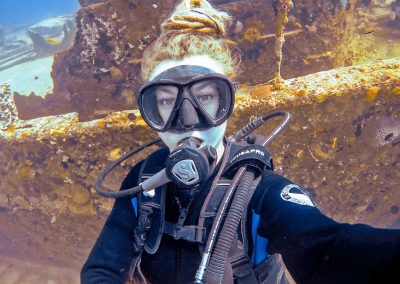 Scuba diving rasta girl in front of shipwreck in Varadero, Cuba