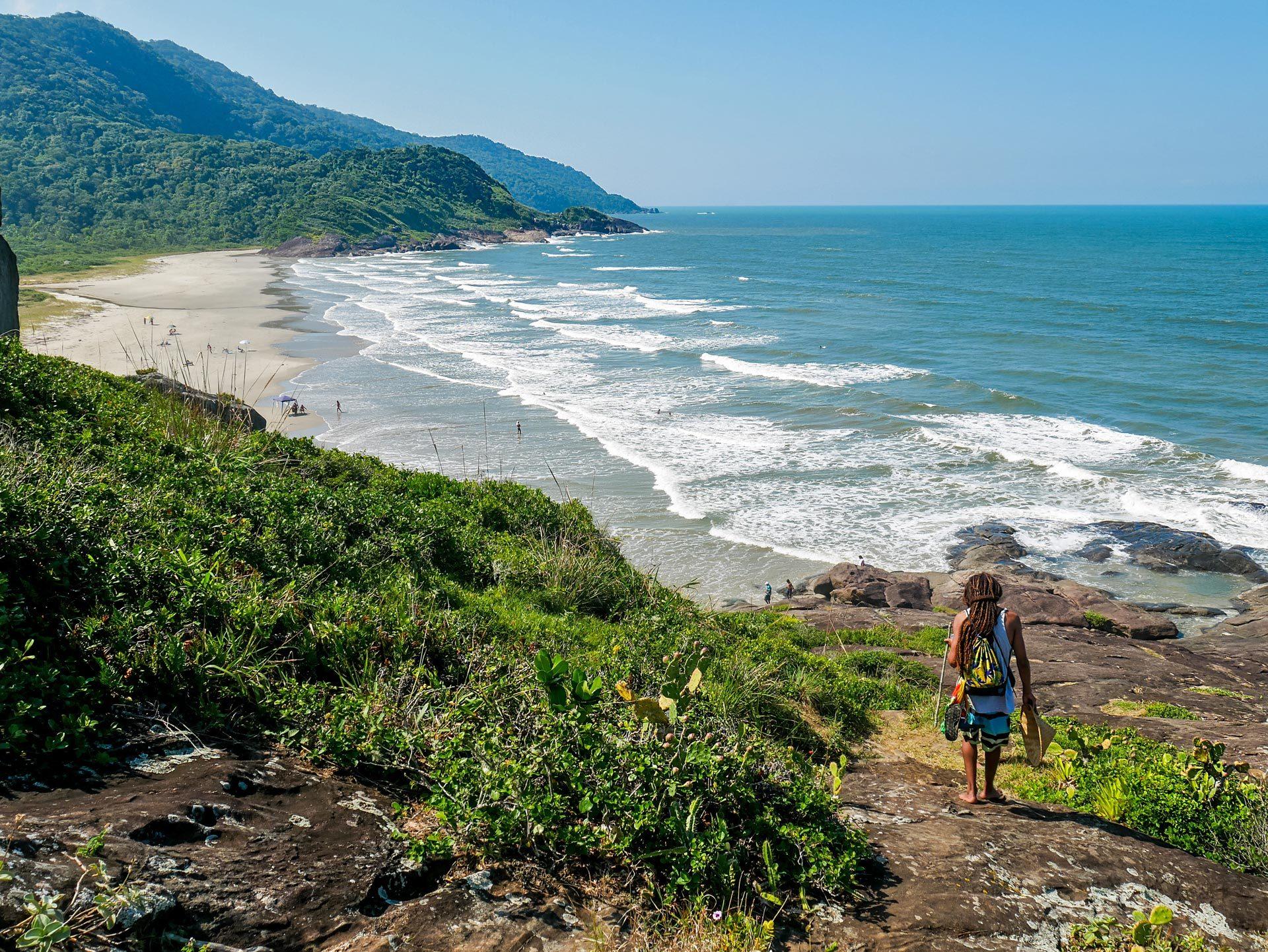 Rastaman hiking on cliff in Barra do Una, Brazil