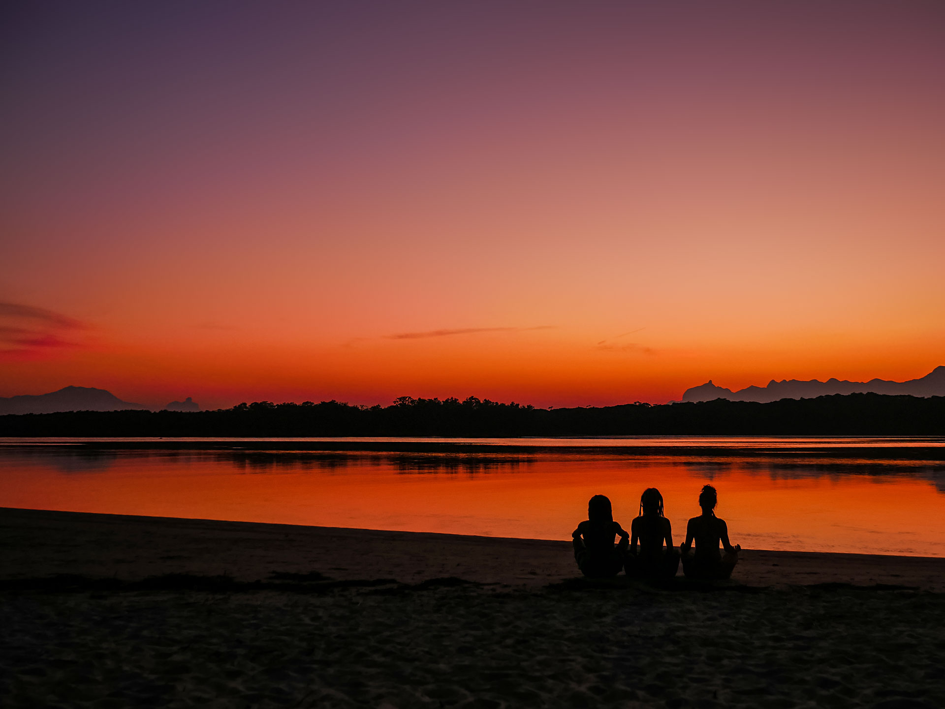 Three friends meditating in front of river with colorful sunset sky in Barra do Una, Brazil
