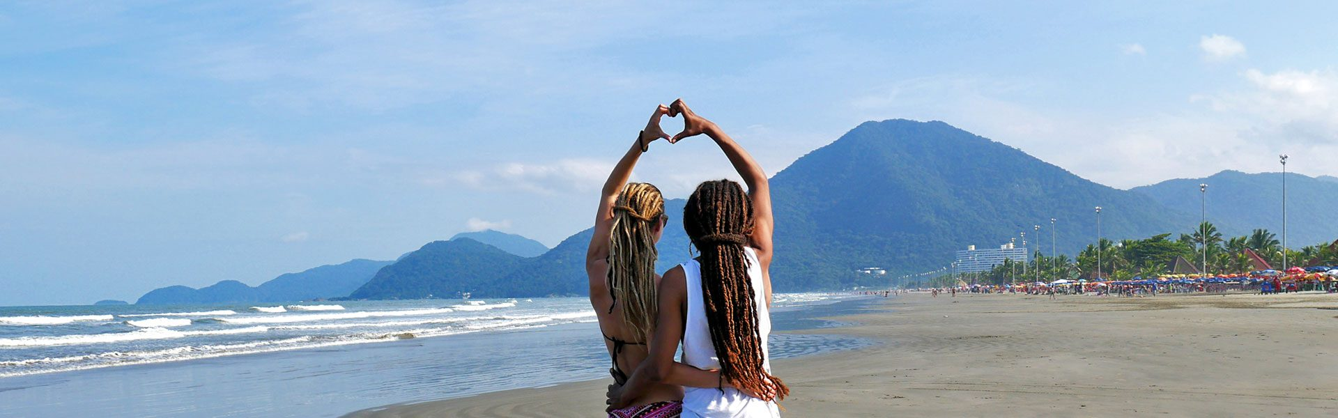 Dreadlock couple forming heart with hands at beach in Peruíbe, Brazil