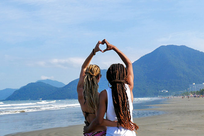 Rasta couple forming heart with hands at beach in Peruíbe, Brazil