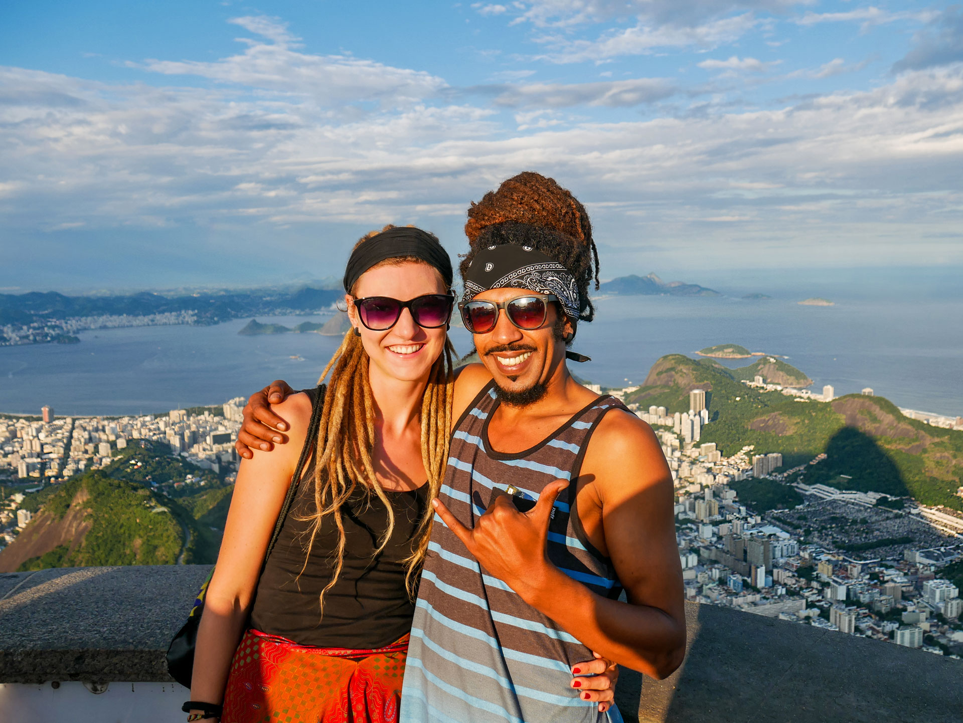 Rasta couple overlooking city and bay from Christ statue in Rio de Janeiro, Brazil