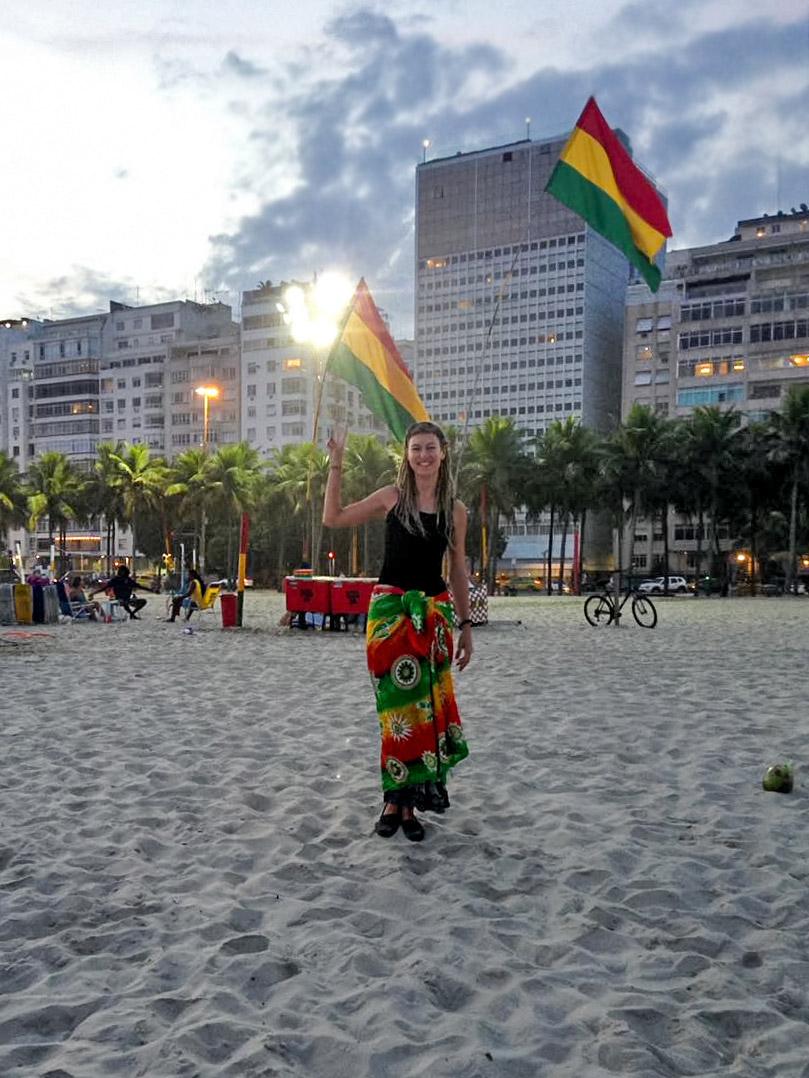 Dreadlock girl in front of rasta flags at Leme beach in Rio de Janeiro, Brazil
