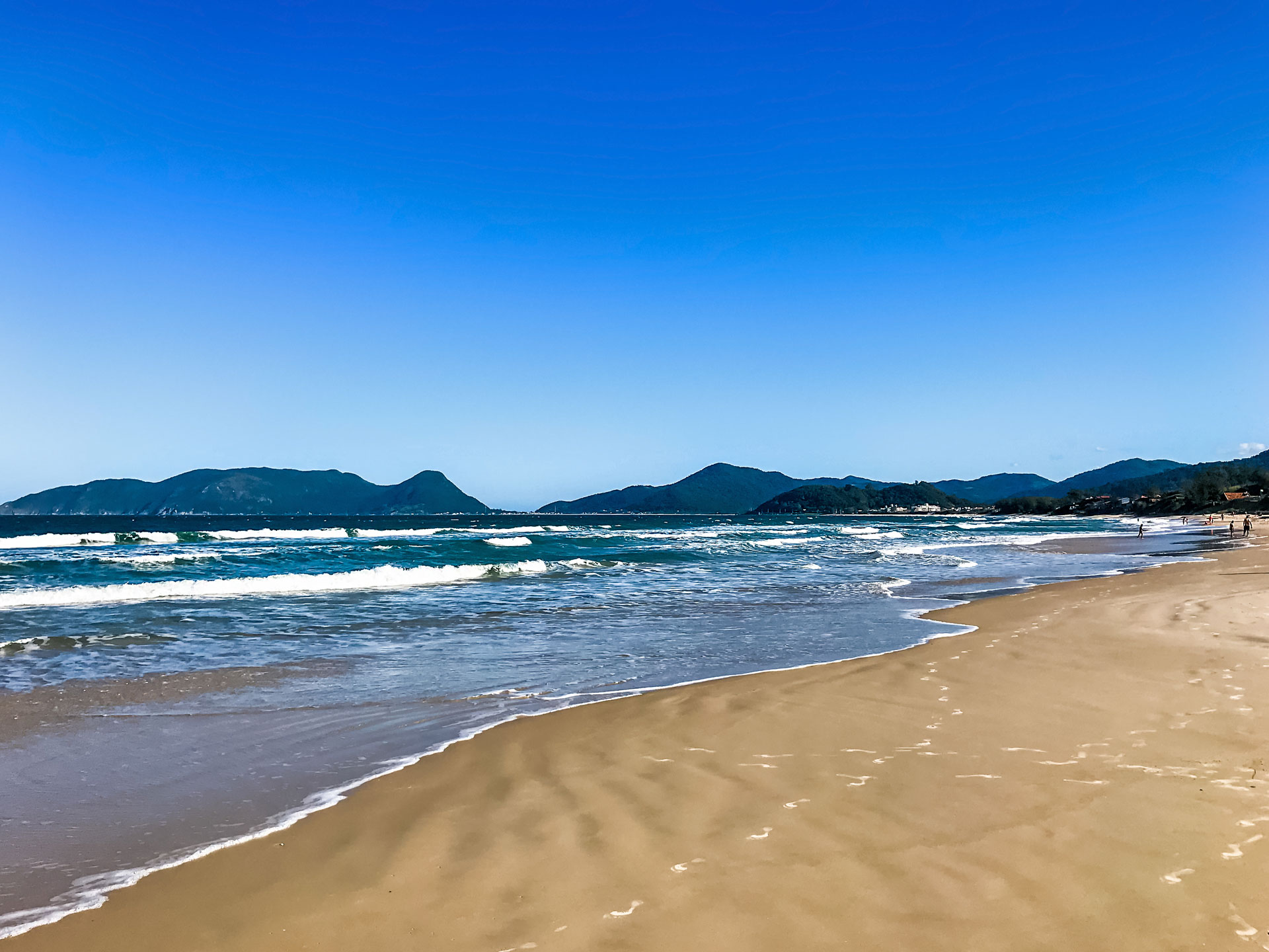 Campeche beach with mountains in background in Florianópolis, Brazil