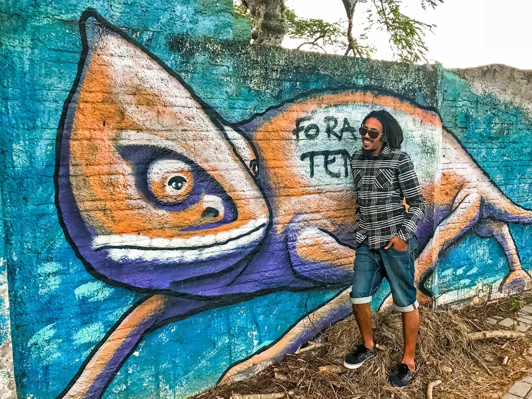 Rastaman in front of chameleon graffiti in Florianópolis, Brazil