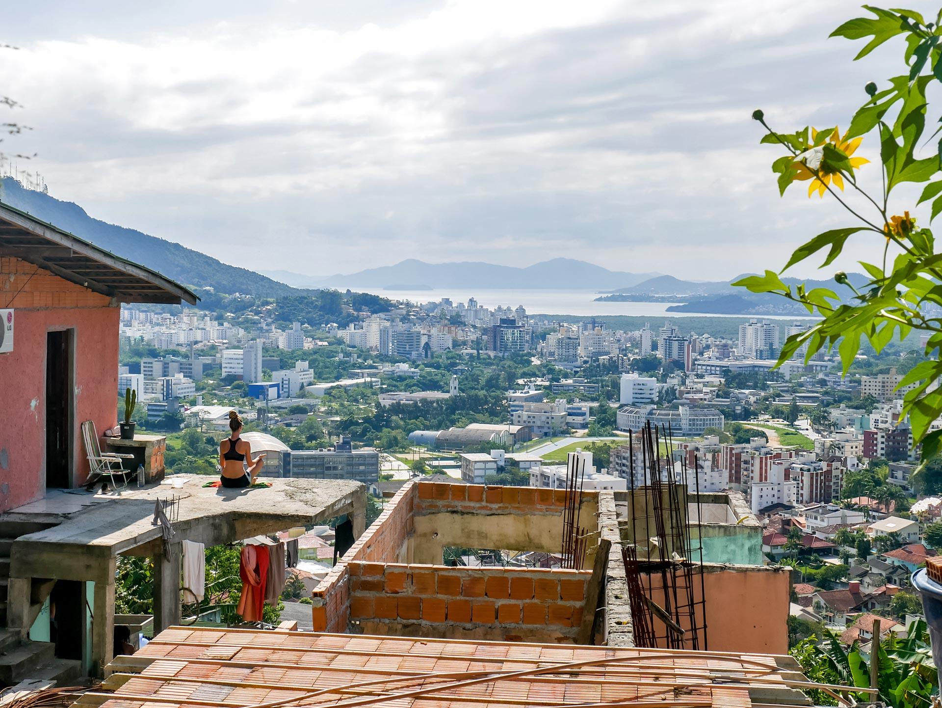 Rasta girl meditating with panoramic view of Florianópolis, Brazil