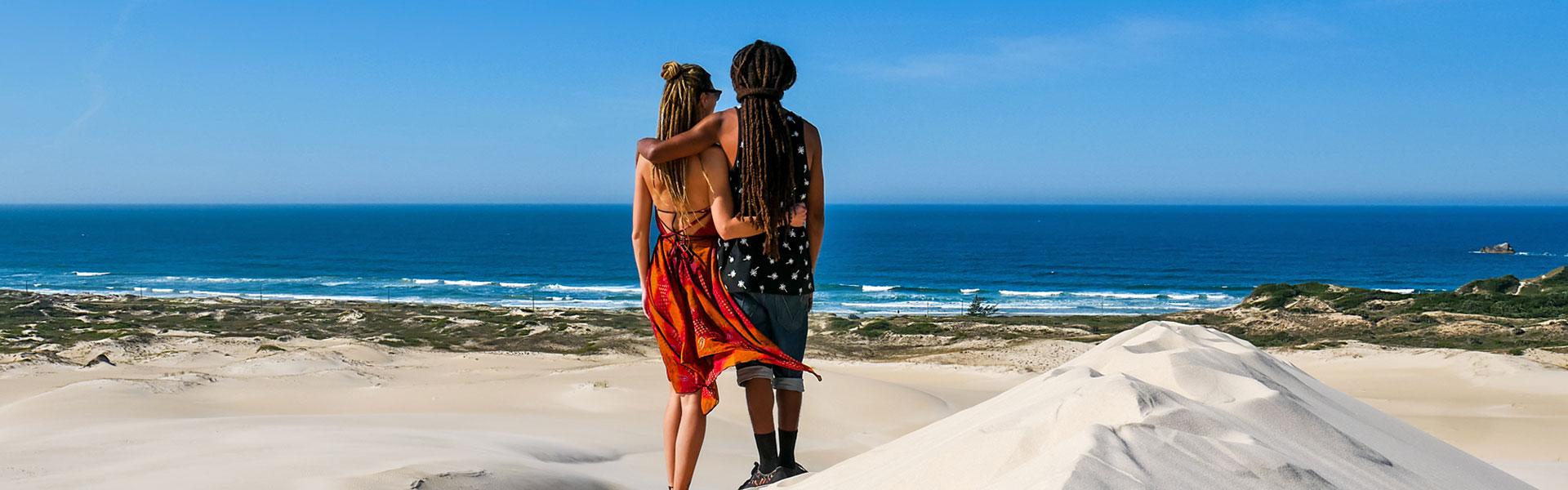 Rasta couple in Dunas da Ribanceira with ocean view in Imbituba, Brazil