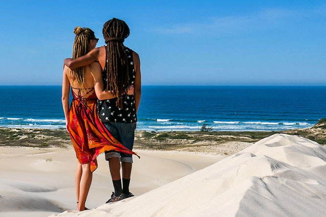 Travel couple in Dunas da Ribanceira with ocean view in Imbituba, Brazil