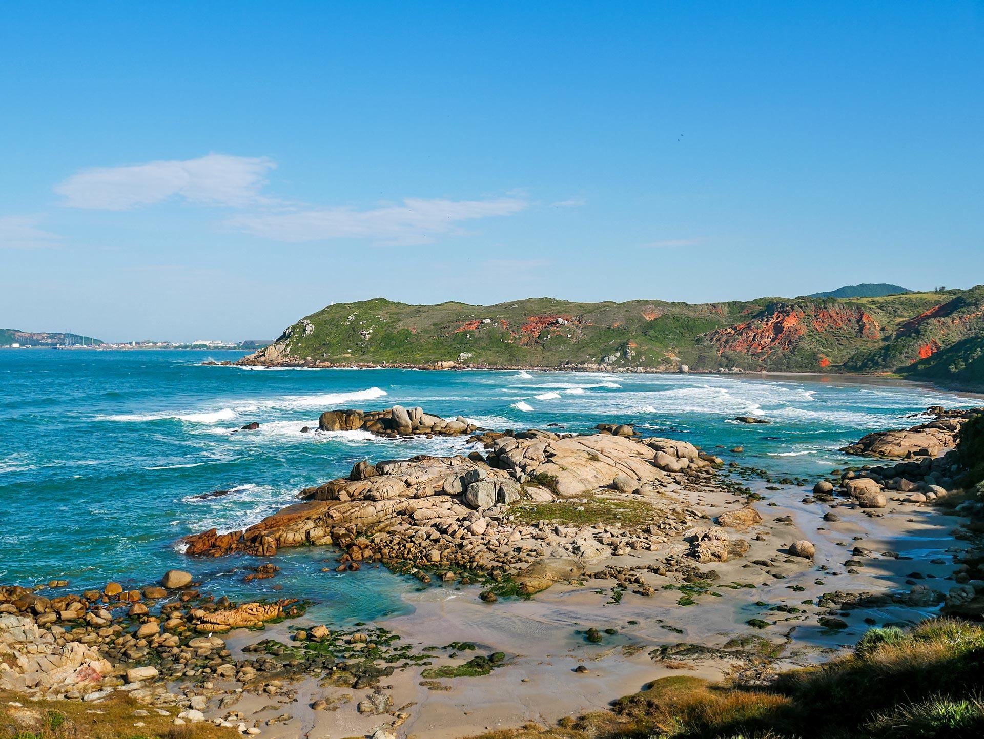 Beach, ocean and surrounding mountains of Praia D'água in Imbituba, Brazil