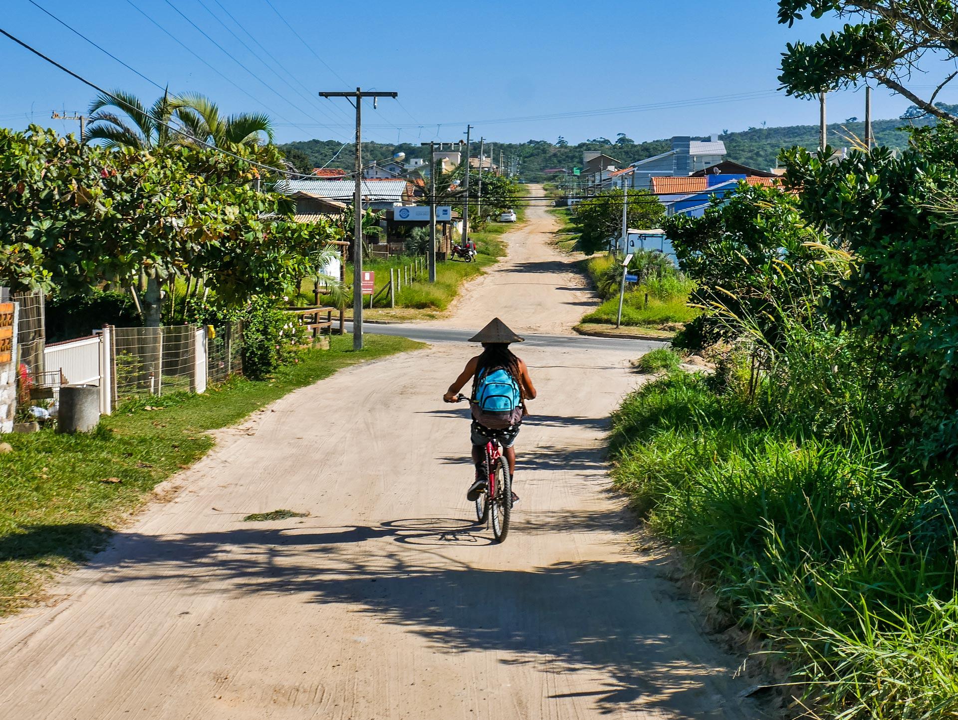 Rastaman riding bike on dirt road in Imbituba, Brazil