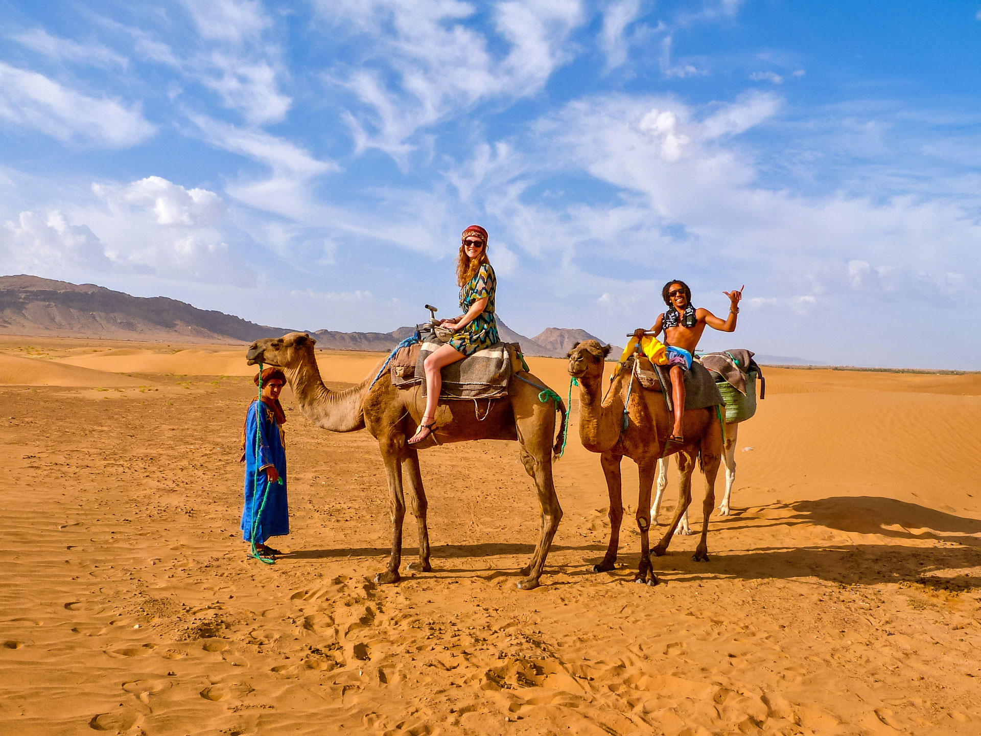 Travel couple on camels in Sahara Desert, Morocco
