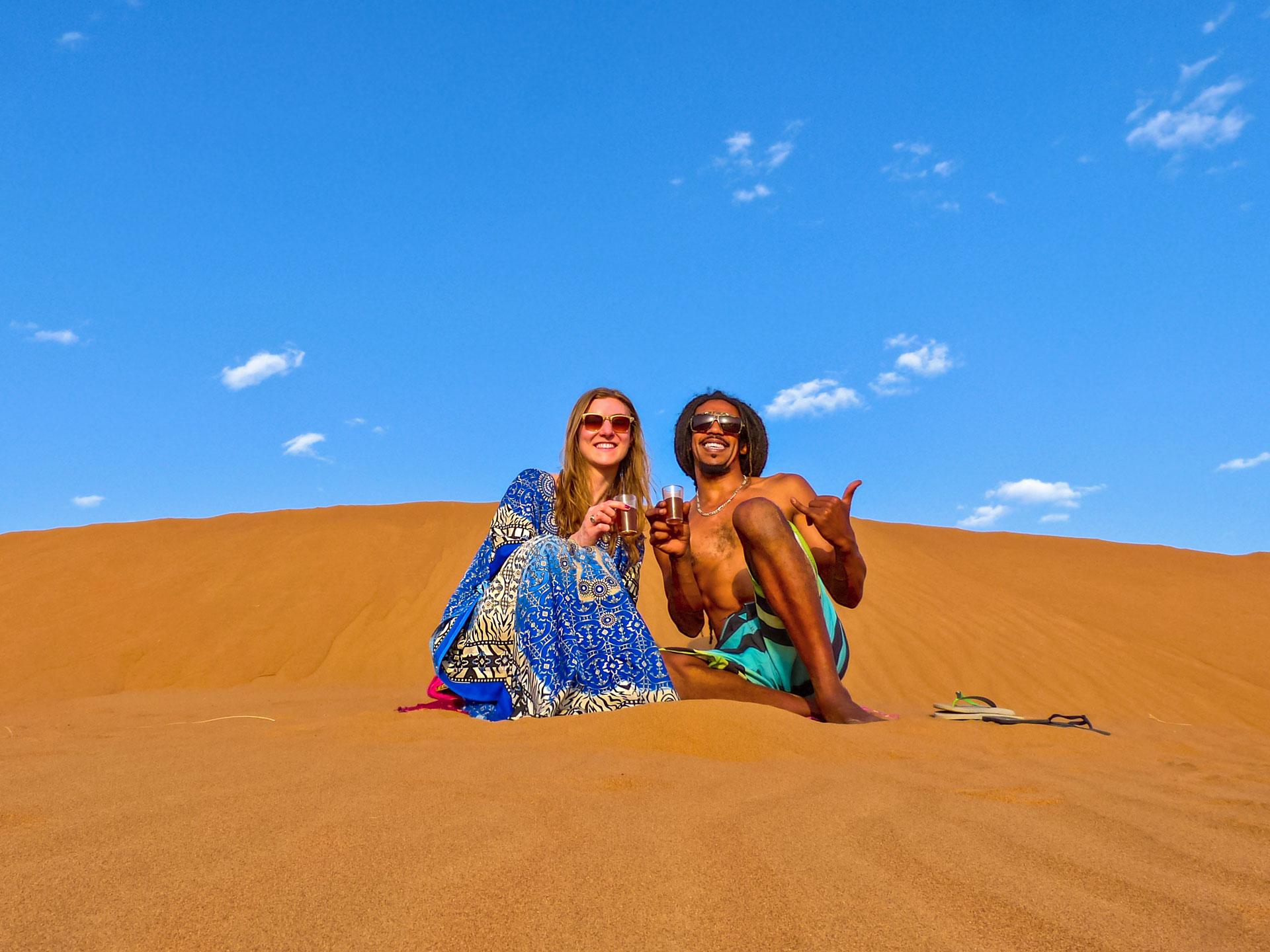 Travel couple with tea in Sahara Desert, Morocco