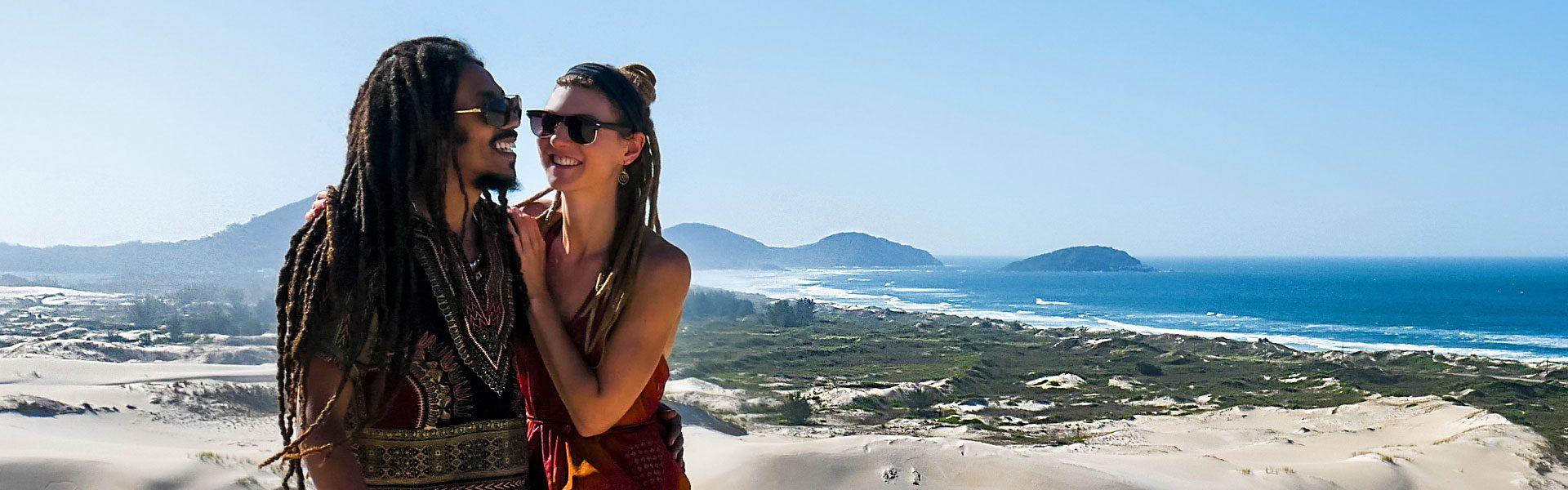 Rasta couple laughing in Dunas da Ribanceira with ocean view in Imbituba, Brazil